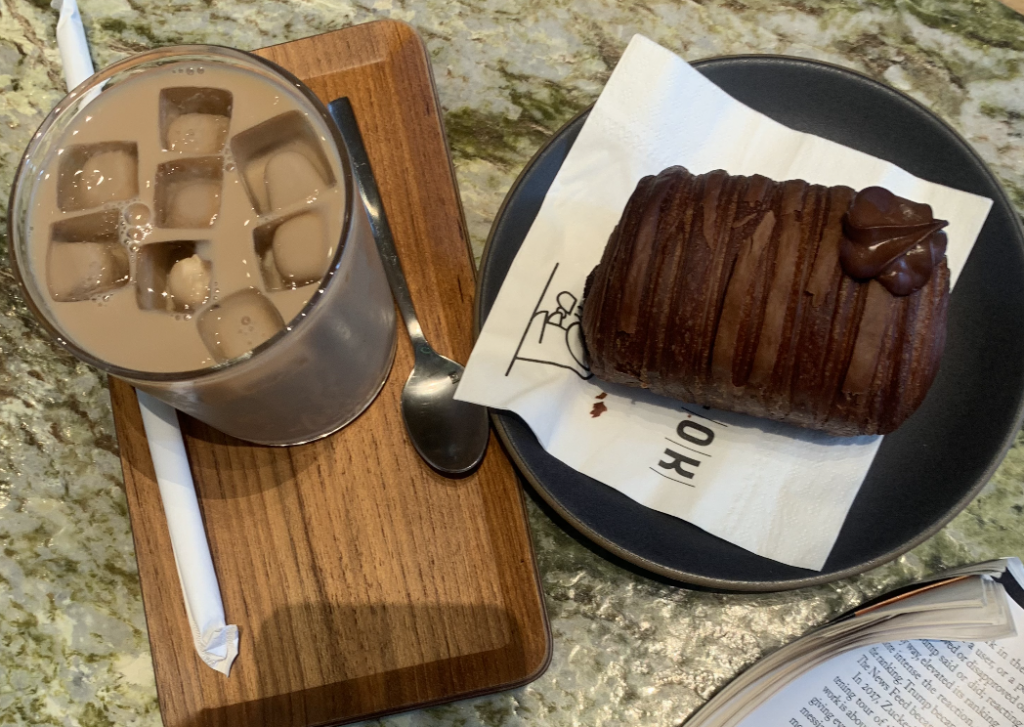 A Hong Kong-style milk tea and a chocolate croissant  on a marble tabletop at A-OK Cafe.