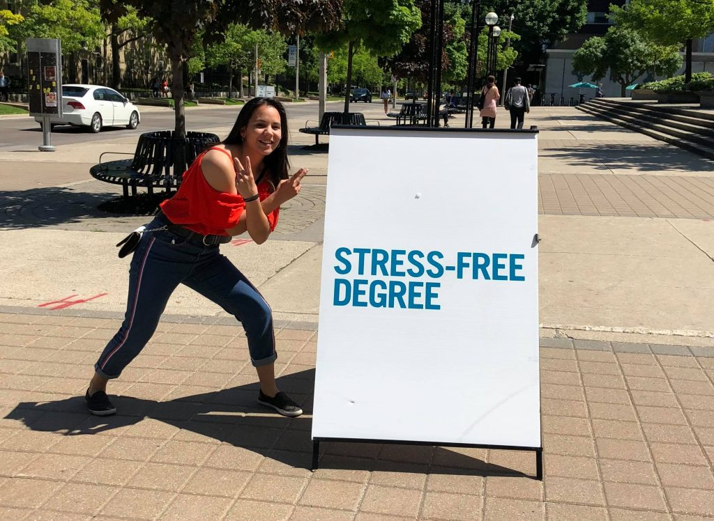 """Future student in front of """"stress-free degree"""" sign"""