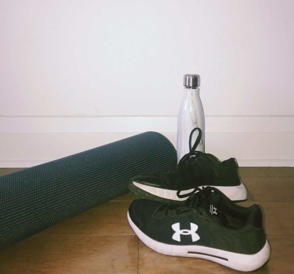 image of a pair of black and white running shoes, a white water bottle and a black yoga mat