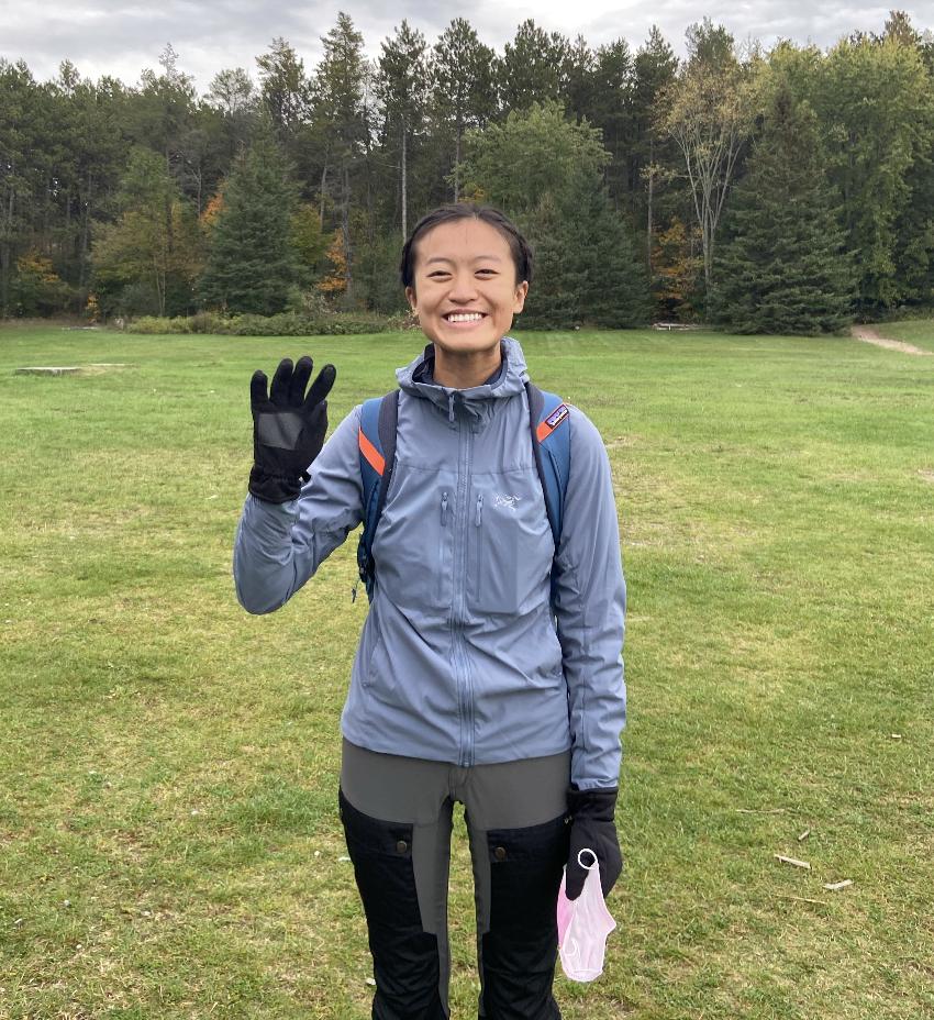 cheryl waving at the camera in hiking gear