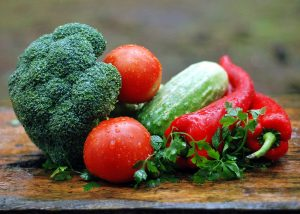 Tomatoes, broccoli, cucumber and pepper on a wooden cutting board