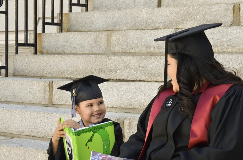 Heather's son smiling while holding a book, looking up at Heather. They are sitting on a set of stone steps and are both wearing graduation caps and gowns.
