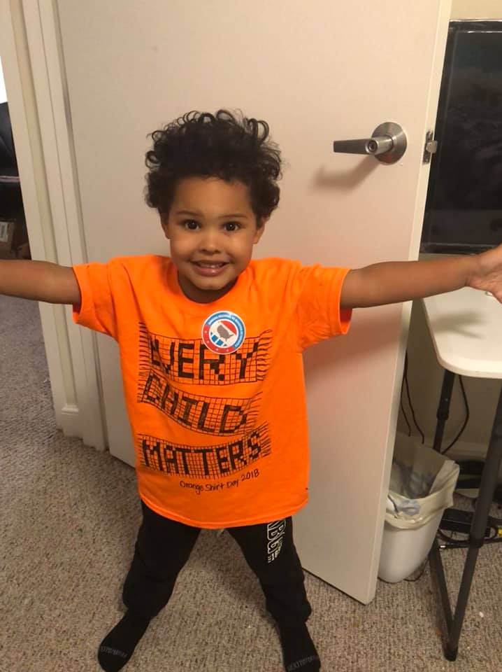 Heather's son smiling to the camera, wearing their orange shirt.
