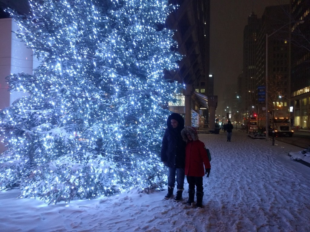 A Toronto city street with lots of snow on the ground and sky scrapers in the background. Shamim's partner and daughter are standing next to a brightly lit Christmas tree with bright blue and white lights.