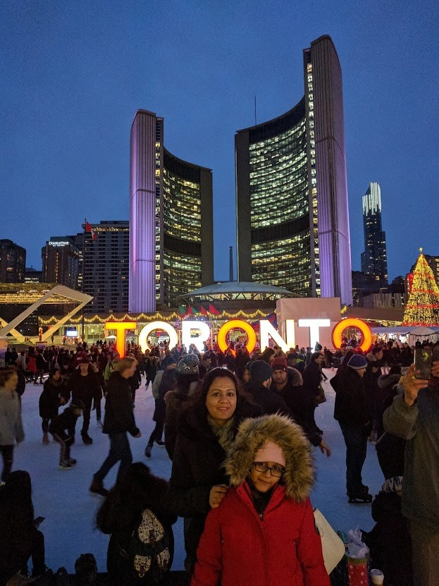 Shamim and his family standing in front of a large and brightly lit Toronto sign, with the cityscape in the background and holiday lights twinkling. There are lots of people ice skating around them.