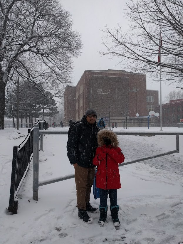 Shamim and his daughter standing infront of her new school, with snow and flurries surrounding them and the school in the background.