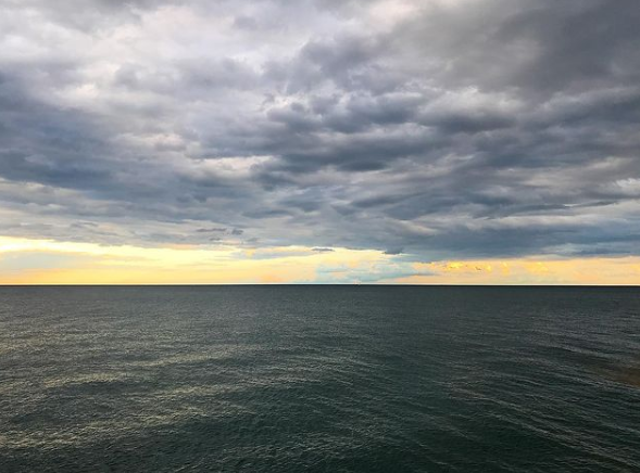 A landscape photo of the ocean, with a colourful sky filled with clouds, making it look like it's about to be stormy.