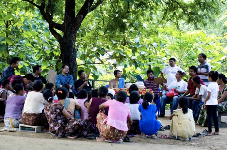 Shamim outside with a group, sitting under a large tree.