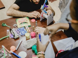 Students using craft supplies such as markers and Play-Do
