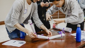 Students building structures out of rolls of paper
