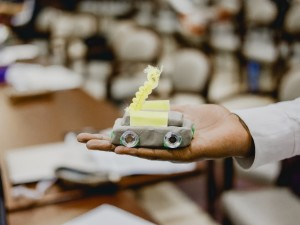 Small car made out of modelling clay in the palm of someone's hand