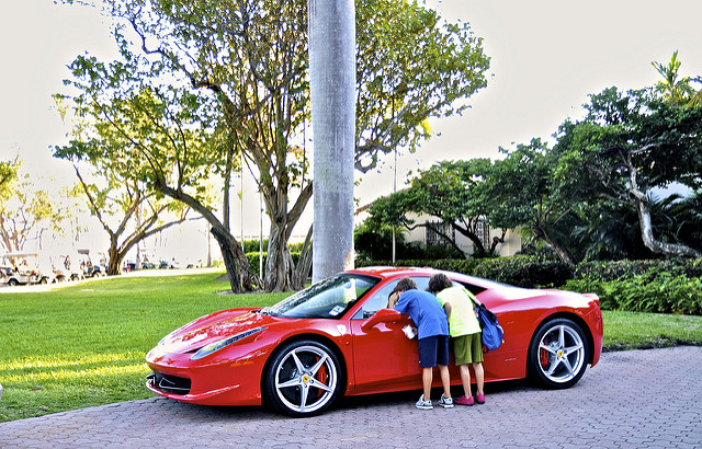 Image of children peeking into window of bright red sportscar.
