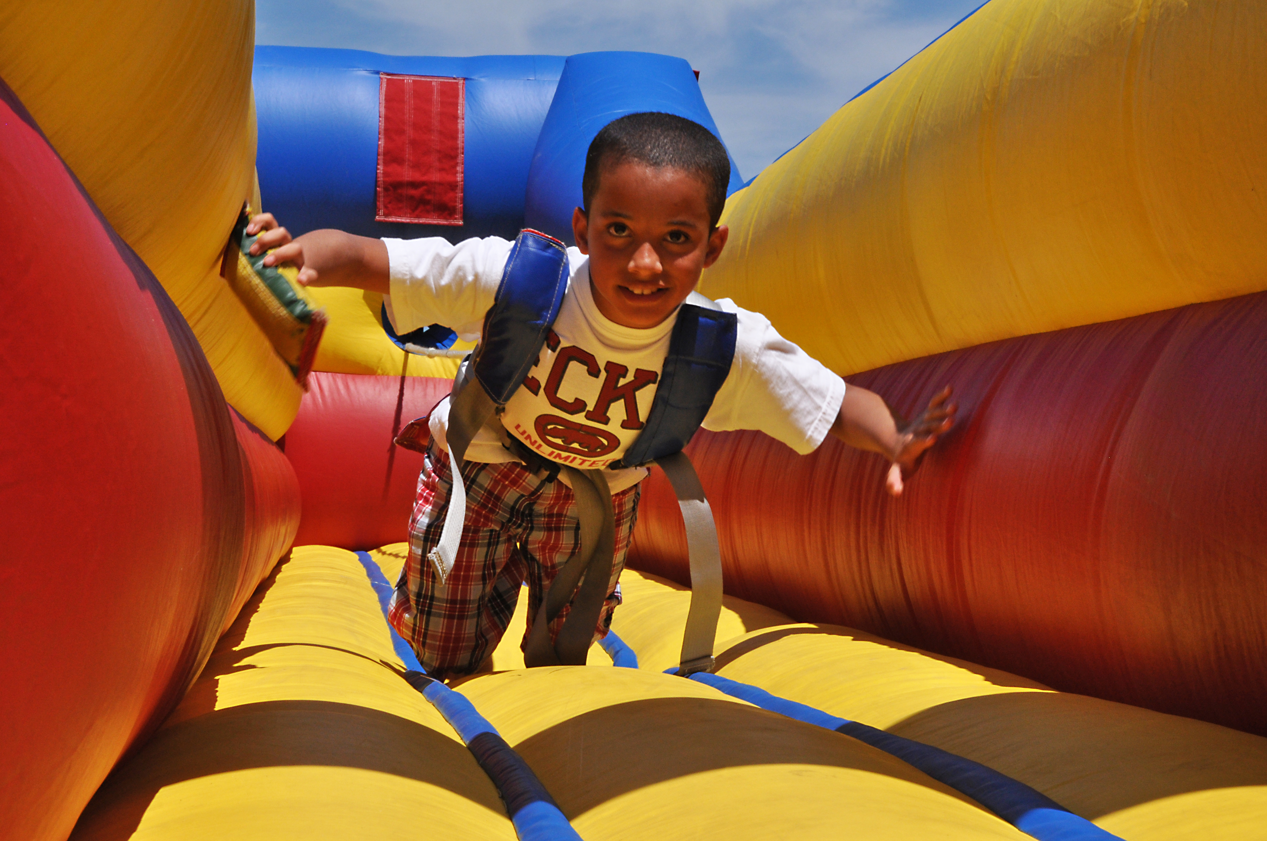 Child playing on a colourful blow up slide