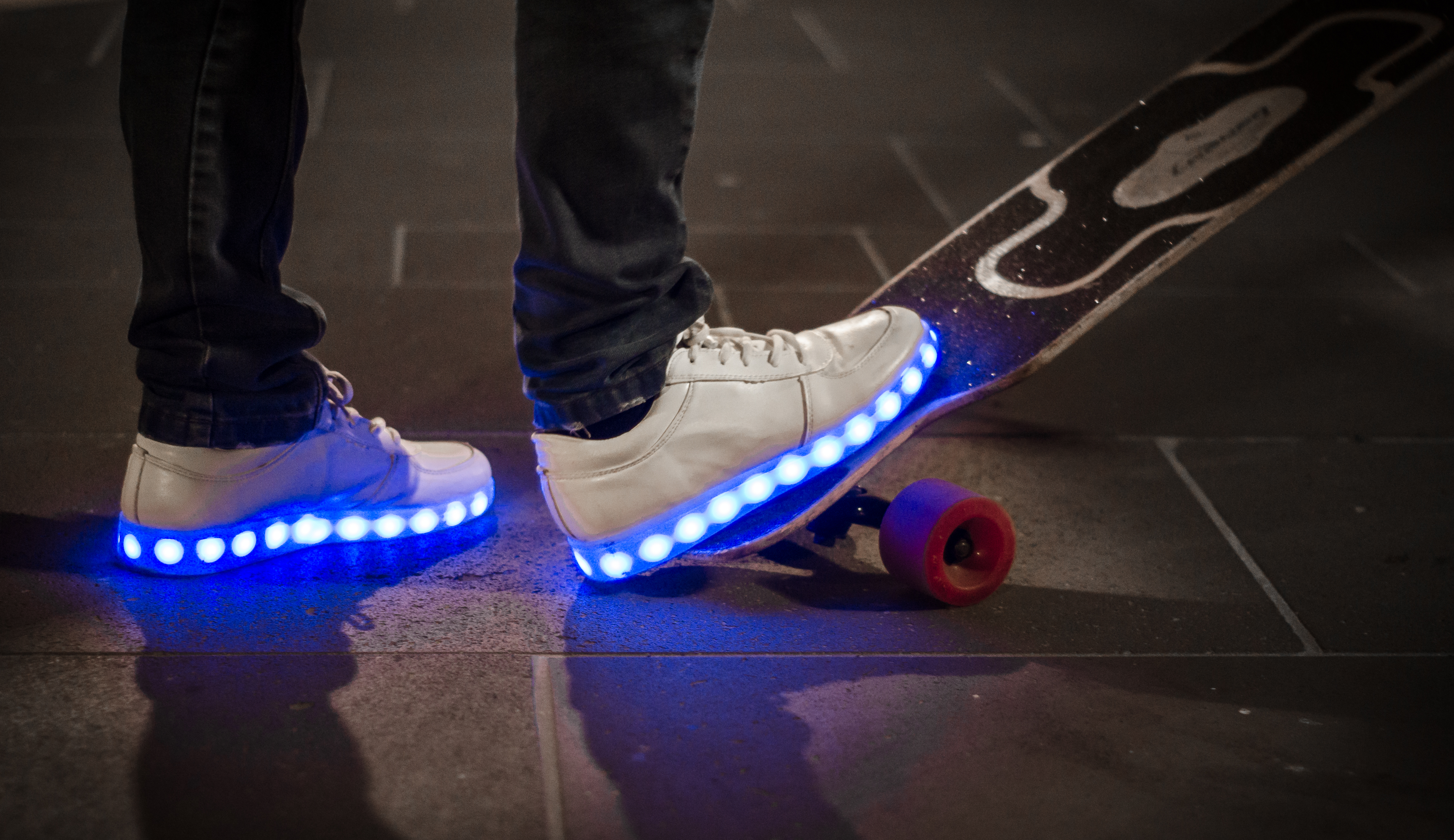 White sneakers with blue LED soles on skateboard.