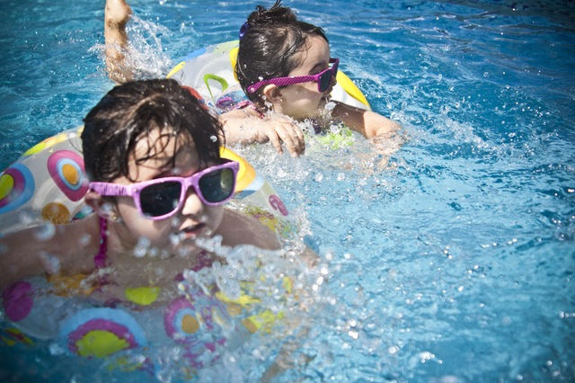 Two small children in pink wayfarer sunglasses swimming in pool floaties