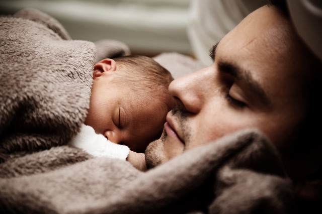 Baby sleeping on father's chest under fuzzy taupe blanket.