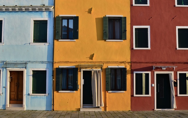 Stucco semidetached houses in blue, yellow, and red
