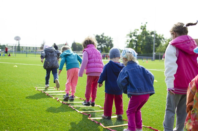 Children play on soft ladder on grass.