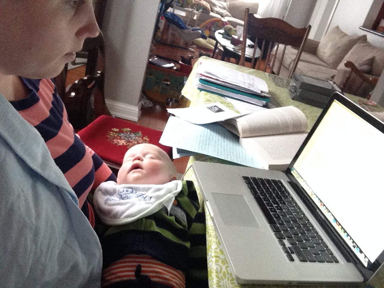 Parent holding baby and studying on laptop.