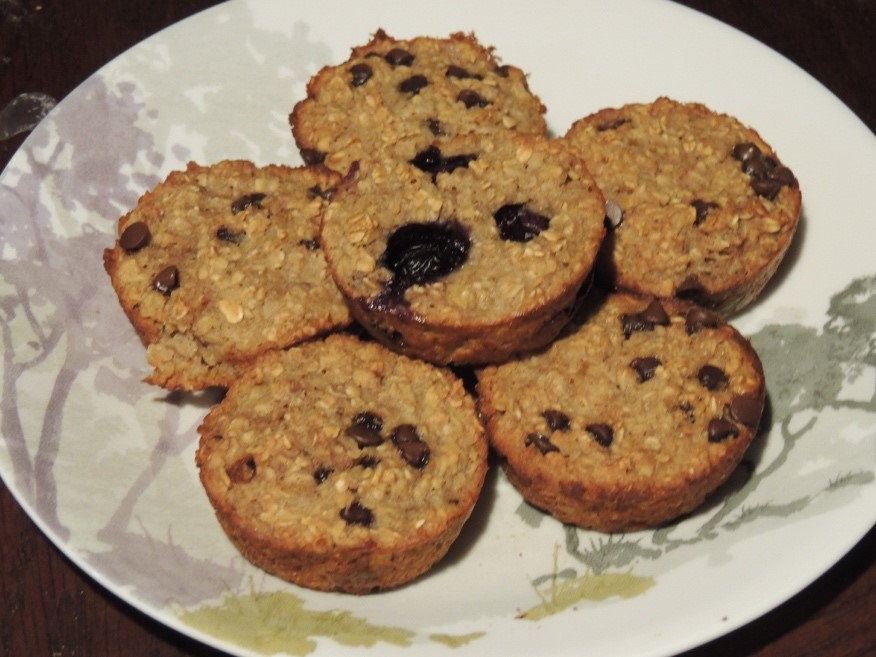 5 muffins sitting on a plate.