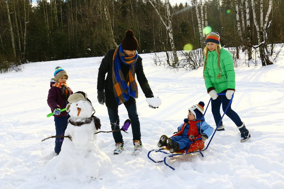 Family of four standing on an ice rink in the winter, building a snowman.