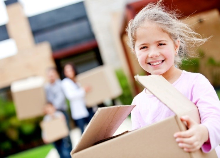 Girl holding moving boxes with her family.
