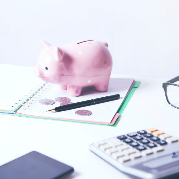 Piggy bank sitting on a notebook with a calculator, pen and glasses on the table.