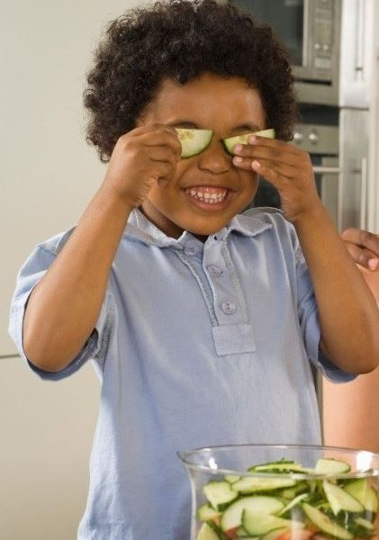 A child holding up sliced cucumbers over his eyes.
