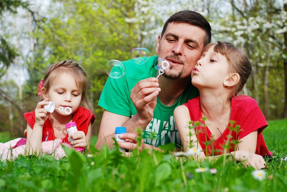 An adult and two children laying on the grass blowing bubbles