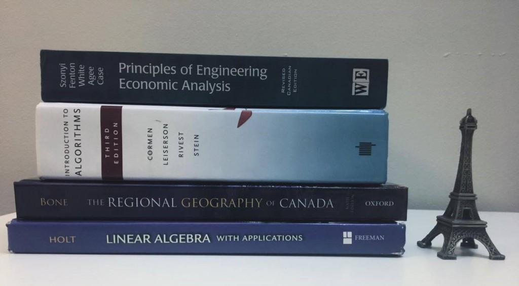 A picture of 4 stacked textbooks next to a miniature Eiffel Tower model