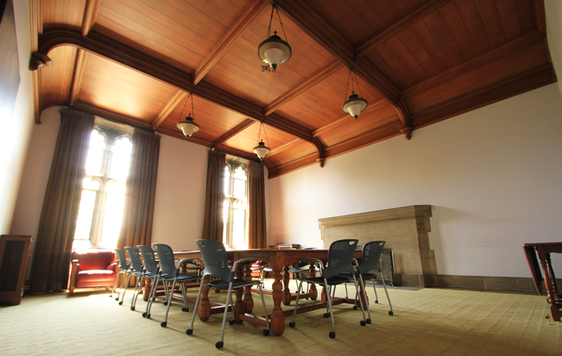 Interior of the Hart House Committees Room. In the foreground: a large, wooden table sits in the center with chairs surrounding it. In the background, the two windows of the room are streaming sunlight in.