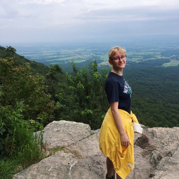 A girl stands on a mountaintop.