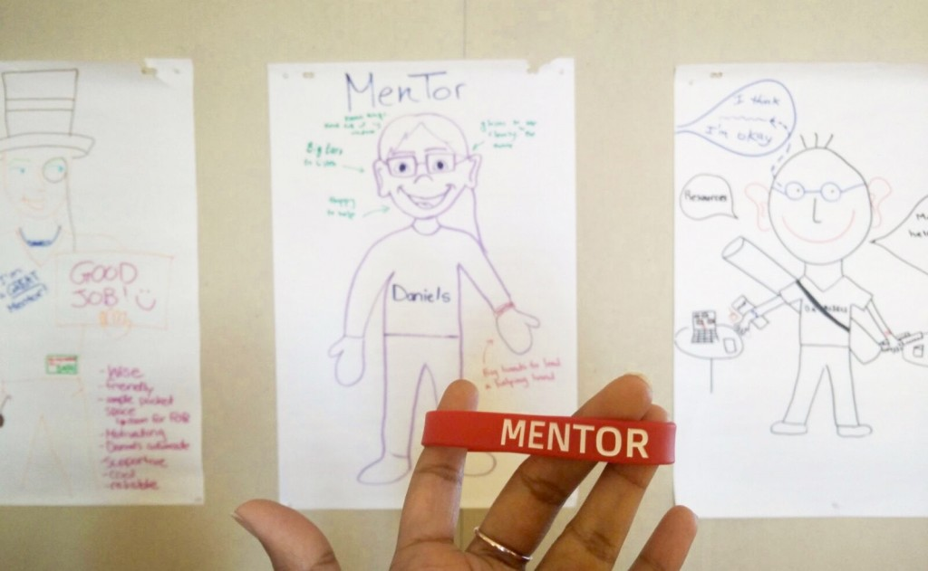 """A picture of a red rubber bracelet with """"Mentor"""" written on it."""