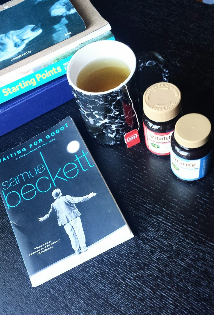 "An image of a mug of tea, two containers of multivitamins and the playbook ""Waiting for Godot"" assorted on a black coffee table."