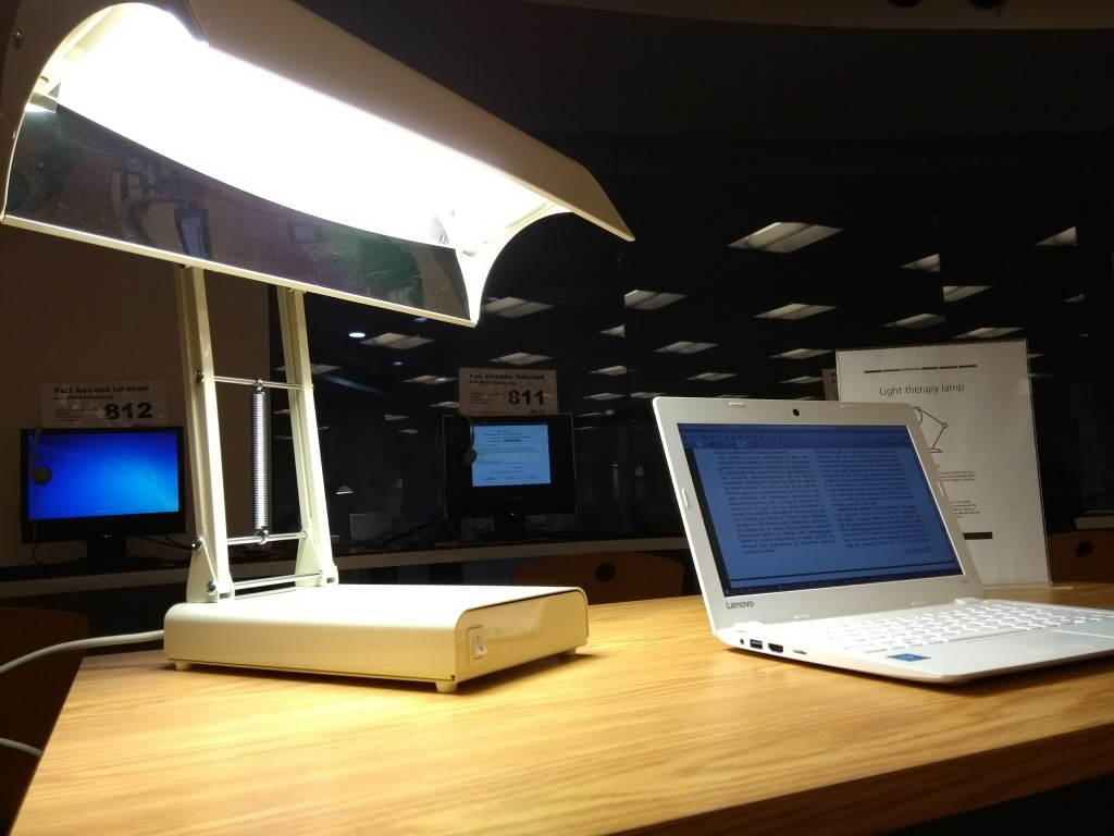 A bright concave-shaped lamp called the Seasonal Affect Disorder (SAD) Lamp on a library desk with a laptop beside it.