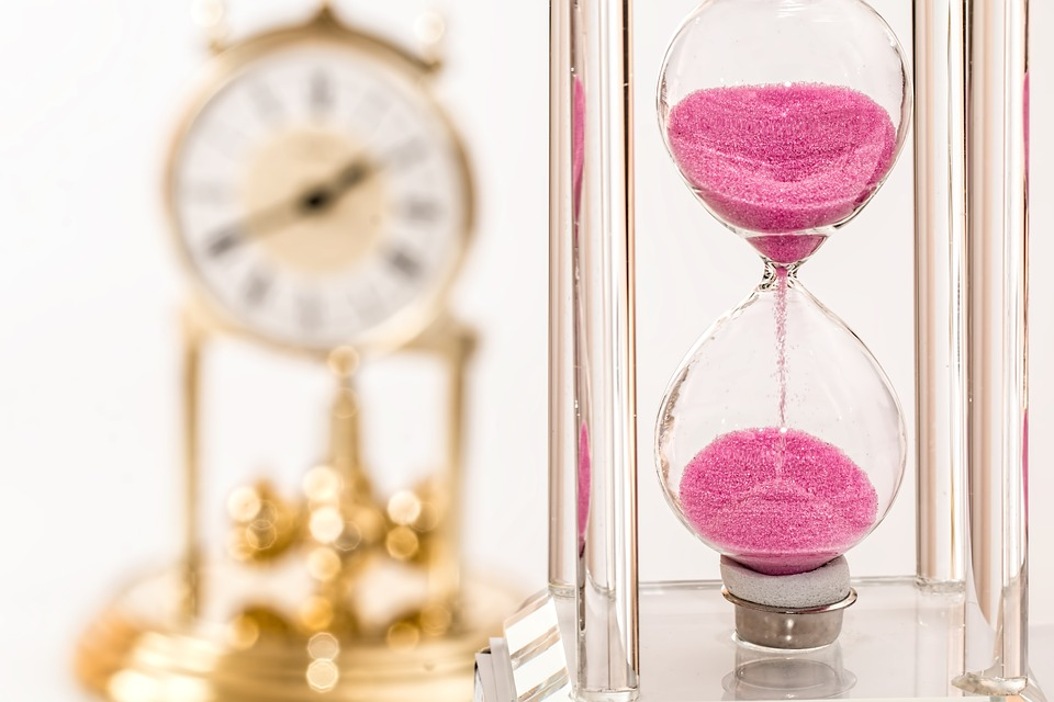 A pink hourglass and gold clock in the background
