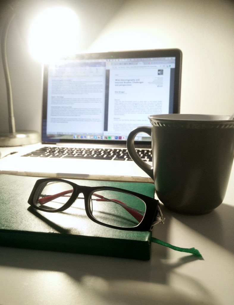 picture of my glasses, journal, coffee cup, lamp, and laptop!