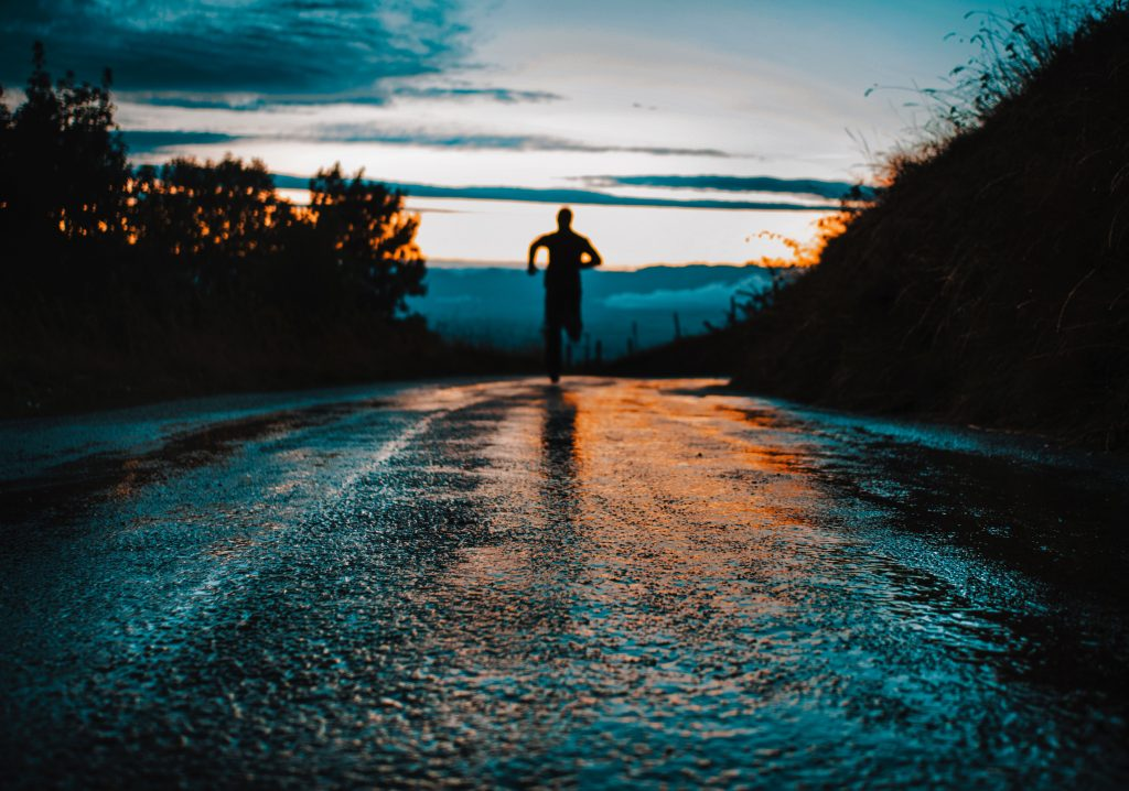 A man runs down a road, away from the camera. He's out of focus and the texture of the road is close-up.