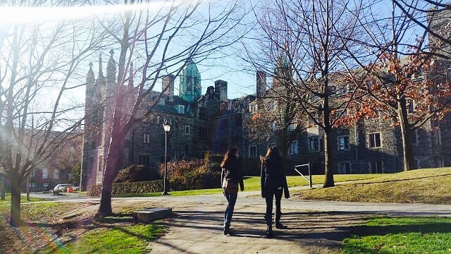Emi and her friend walking on Trinity grounds.