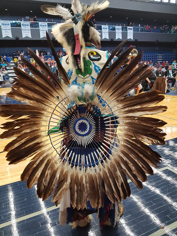 Photo of pow wow dancer with eagle feather regalia