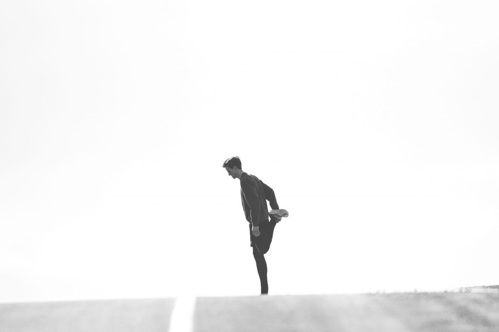 A man stretches his thigh before running on a black and white road.