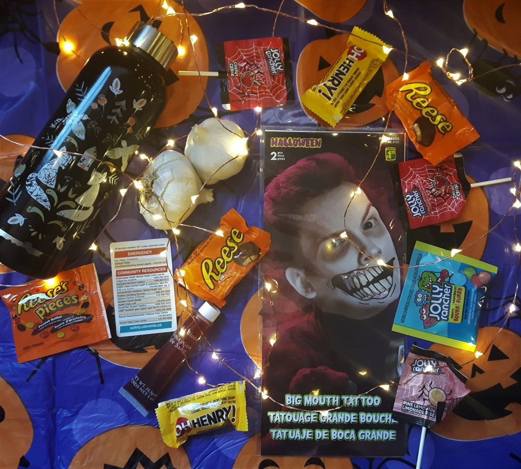On a purple and orange pumpkin tablecloth, there's a waterbottle, two cloves of garlic, a temporary scary smile face tattoo, a tube of fake blood, a card that lists emergency resources around the community, and a bunch of candy. This is all surrounded by a string of lights.