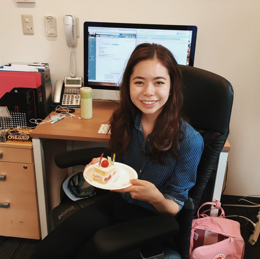 Emi sitting in office holding birthday cake.