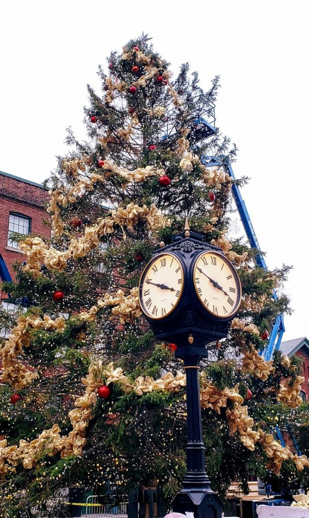 A picture of a Christmas tree and a standing clock in the Distillery District of Toronto