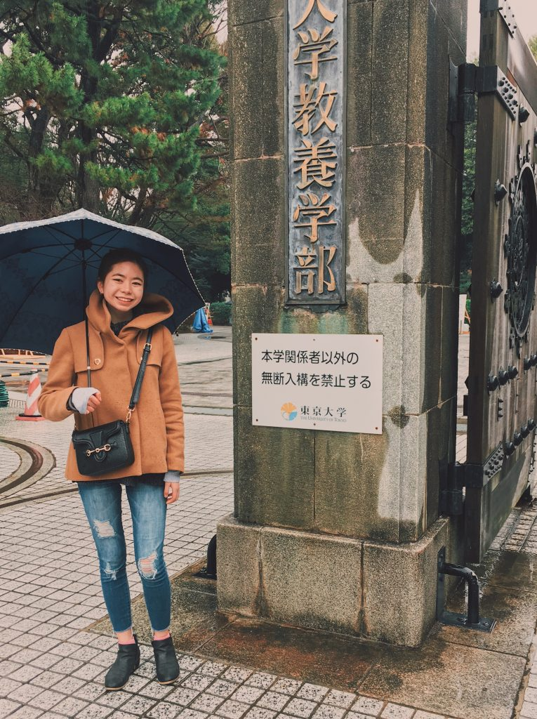 Emi, holding an umbrella, standing in front of the University of Tokyo entrance gate.