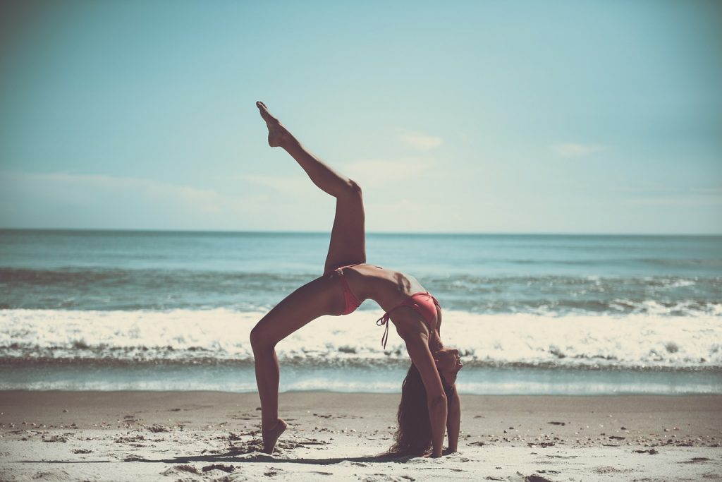 Image of woman doing a yoga pose on the beach