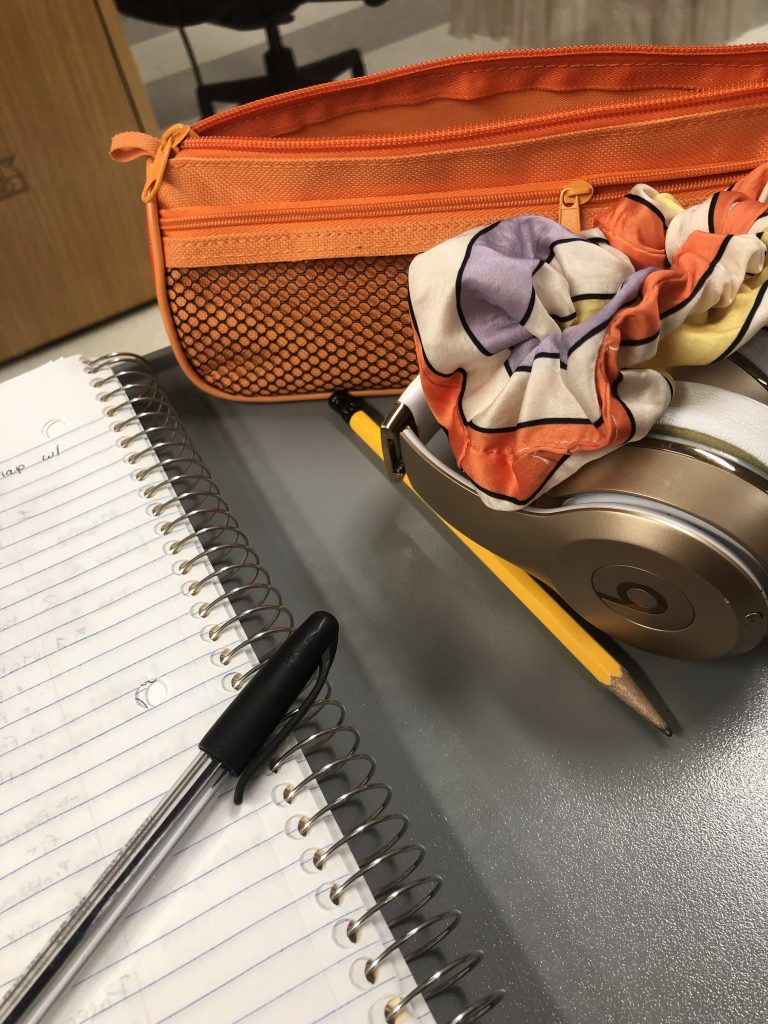 A notebook with a pen lying over it is set down next to an orange pencil case, a pencil, a set of headphones, and a scrunchie.