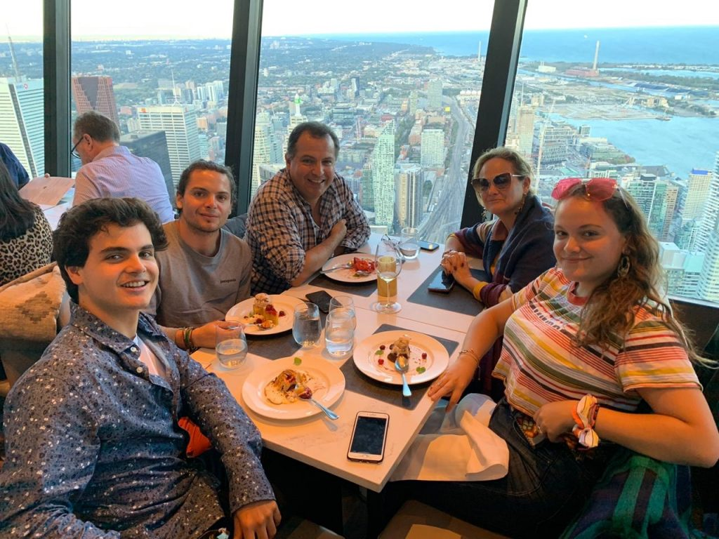 Francesca and her family having dinner on the CN Tower. They're all looking at the camera.