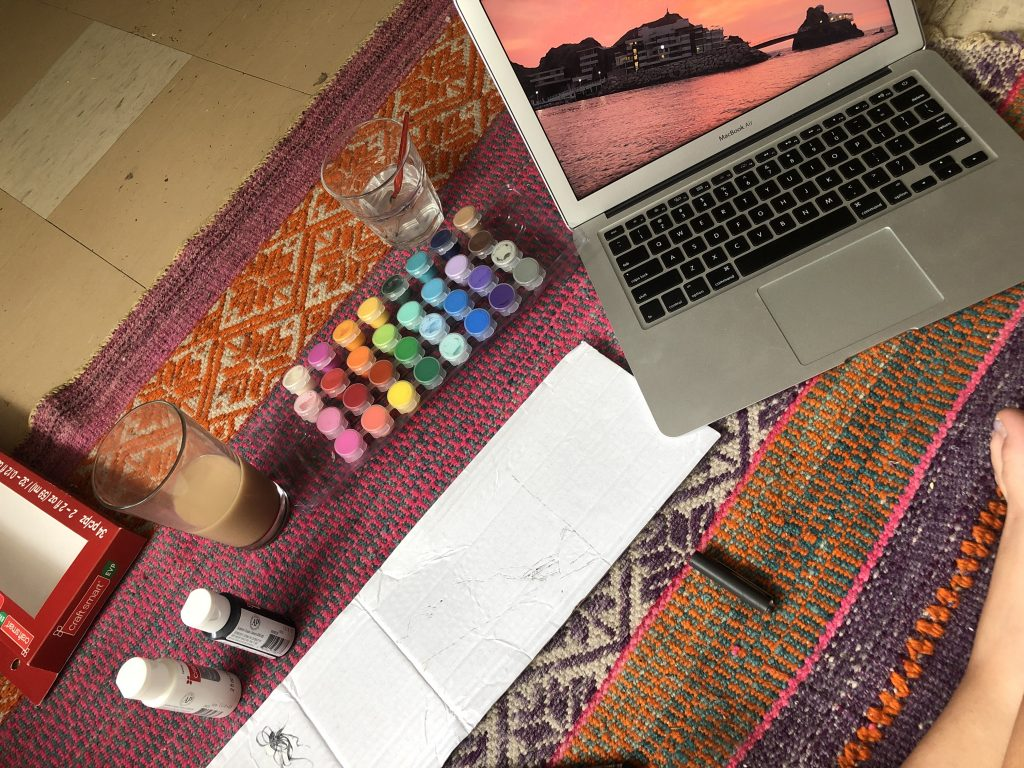 On a colourful carpet acrylic paint is setup next to a laptop with the image of a sunset open on it.