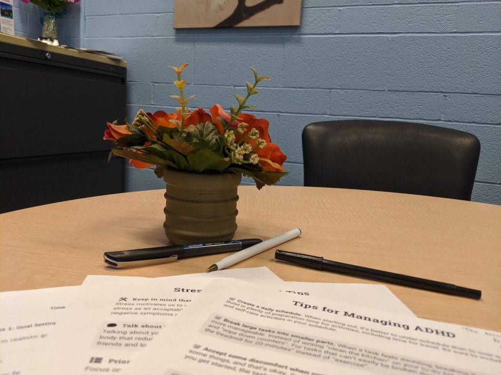 A few sheets on a desk with a small red plant and a blue brick wall
